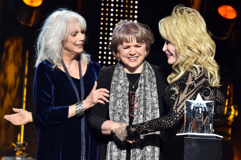 Emmylou Harris and Linda Ronstadt present Dolly Parton with an award at MusiCares Person of the Year in Los Angeles, California on February 8, 2019 | Photo: Getty Images