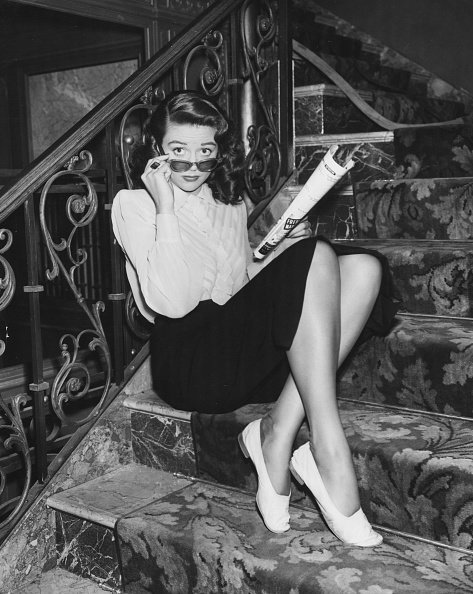 Dorothy Malone sitting on a staircase reading a magazine, and wearing sunglasses, circa 1940. | Photo: Getty Images
