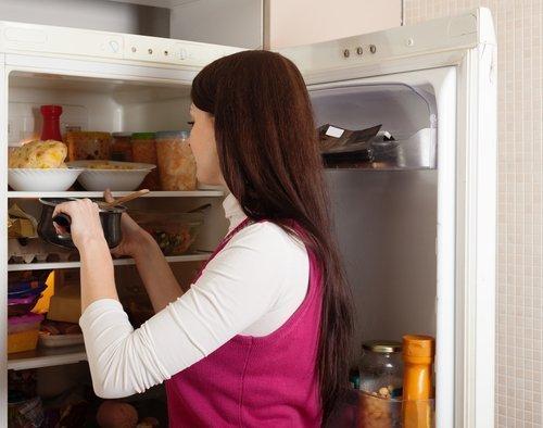 Frau nimmt Essen aus Kühlschrank | Quelle: Shutterstock