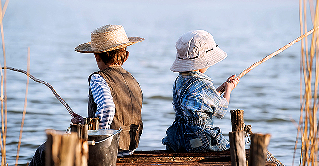 Daily Joke: Two Boys Chat While Fishing on the Bank of a River