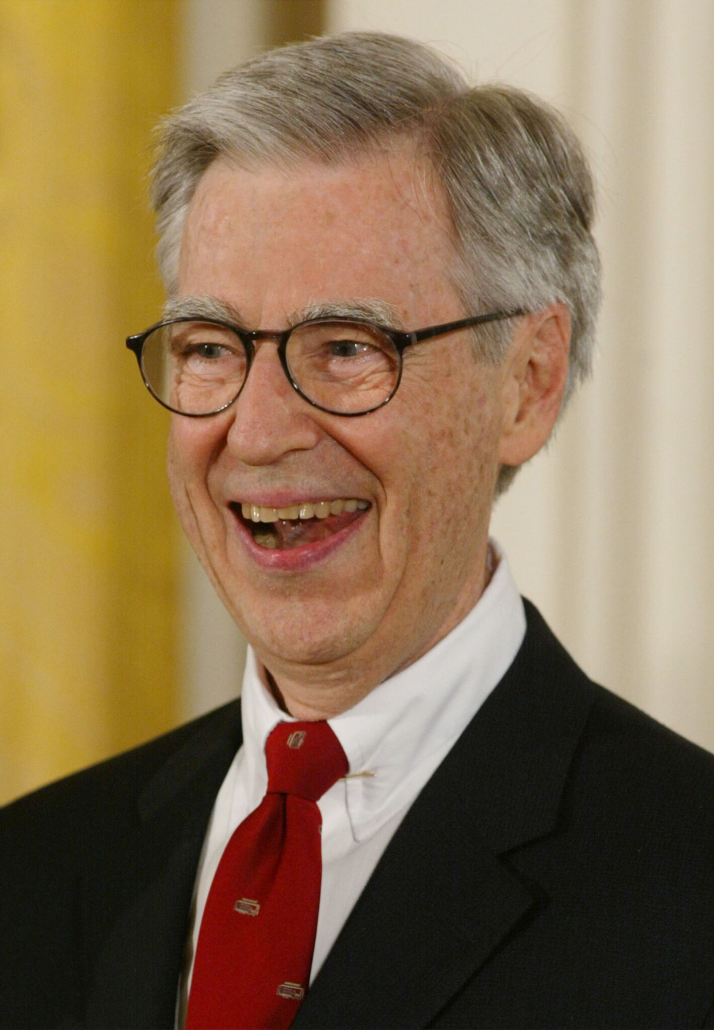 Fred Rogers smiles after receiving the Presidential Medal of Freedom Award from U.S. President George W. Bush, during a ceremony at the White House | Getty Images / Global Images Ukraine