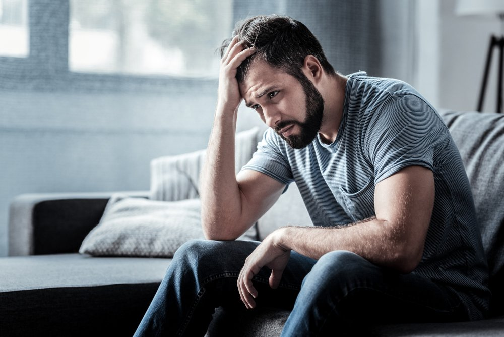 A sad unhappy man sitting on the sofa and holding his forehead. | Photo: Shutterstock