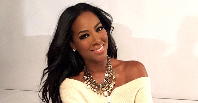 RHOA Star Kenya Moore Looks Awesome Posing in a Trendy White Coat & Translucent Heels