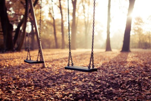 Two swings on playground in sunlight.| Photo: Getty Images