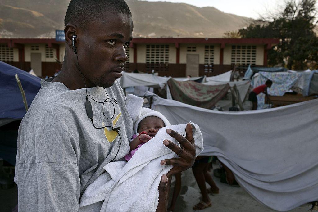 Homme tenant son bébé dans ses bras | Getty Images