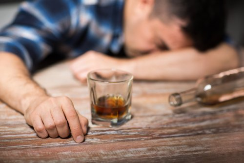A man sleeping with his head on the table after drinking alcohol. | Source: Shutterstock.