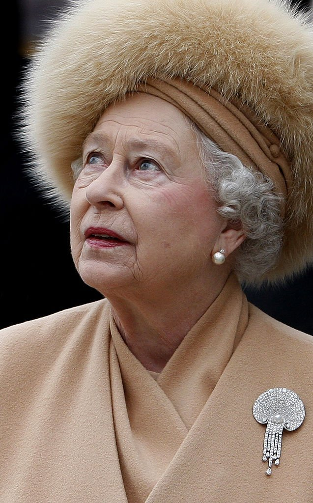 Queen Elizabeth II looks up at the statue of her mother as she attends the unveiling of a new statue of Queen Elizabeth, the Queen Mother on the Mall on February 24, 2009, in London, England. | Source: Getty Images.