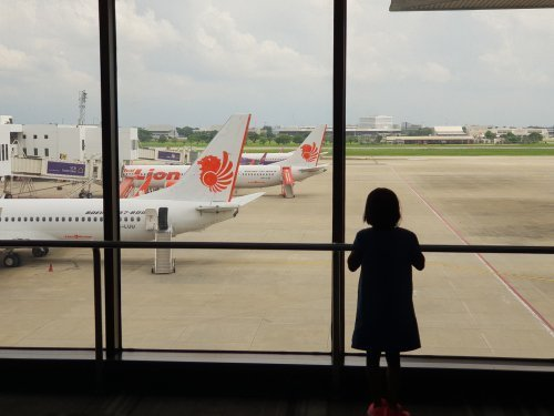 Little girl staring out of an airport window. | Source: Shutterstock