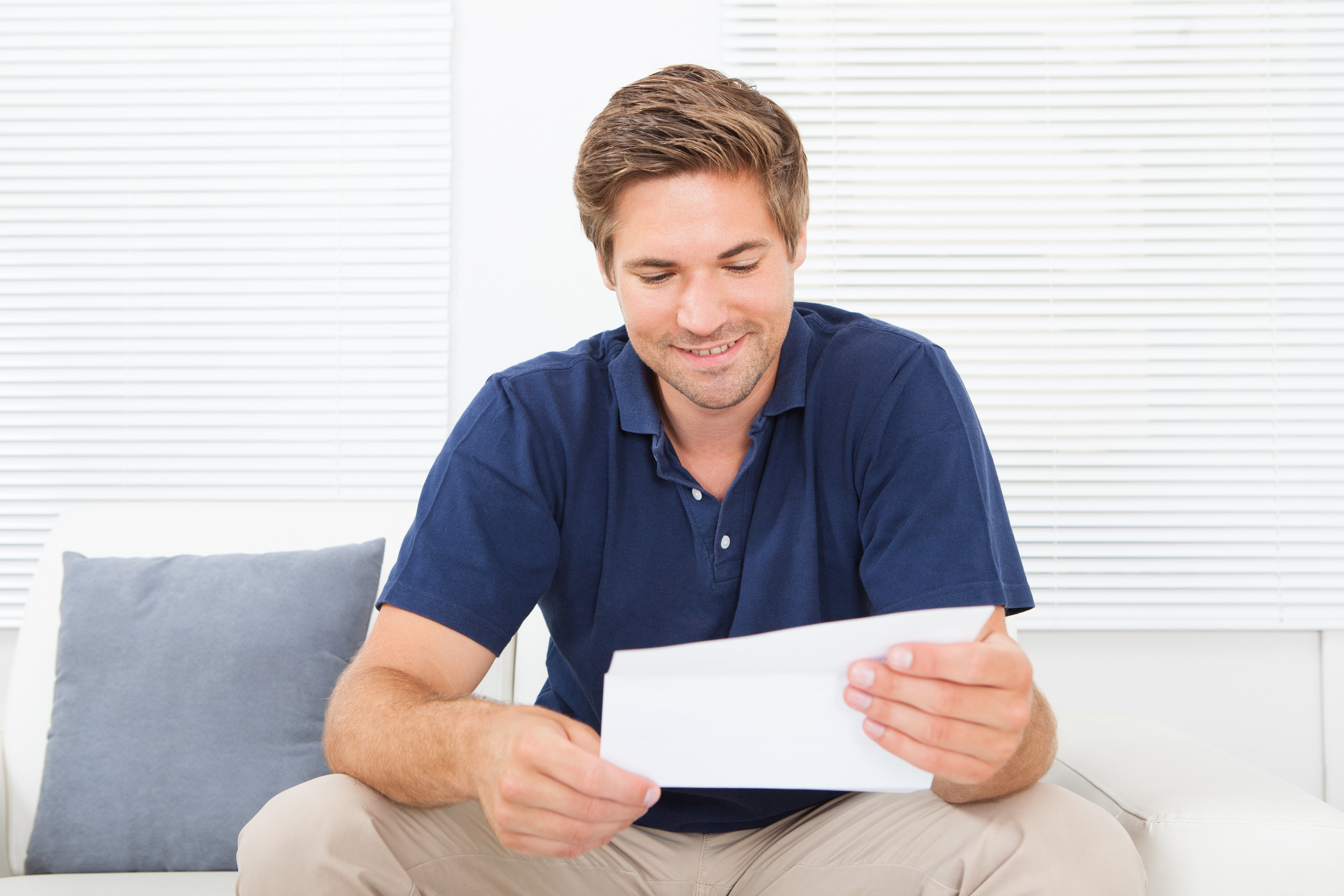 Smiling mid adult man reading letter while sitting on a sofa | Photo: Shutterstock.com