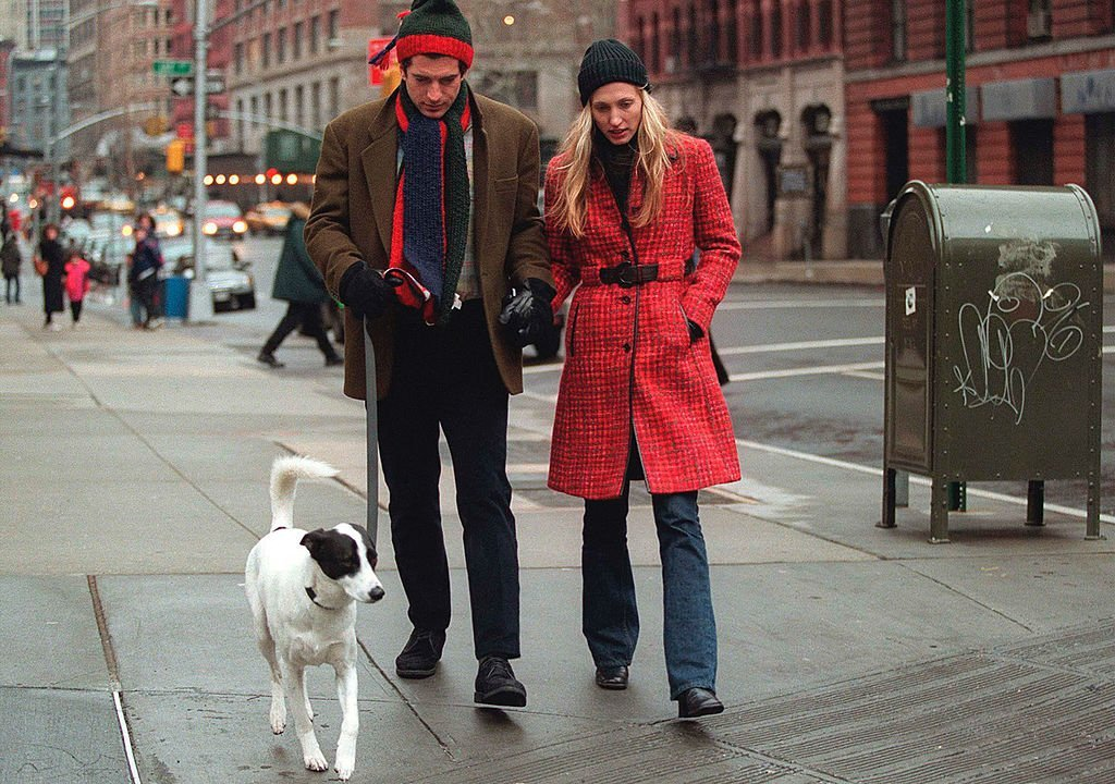 John F. Kennedy Jr. and his wife Carolyn walk with their dog | Photo: Getty Images
