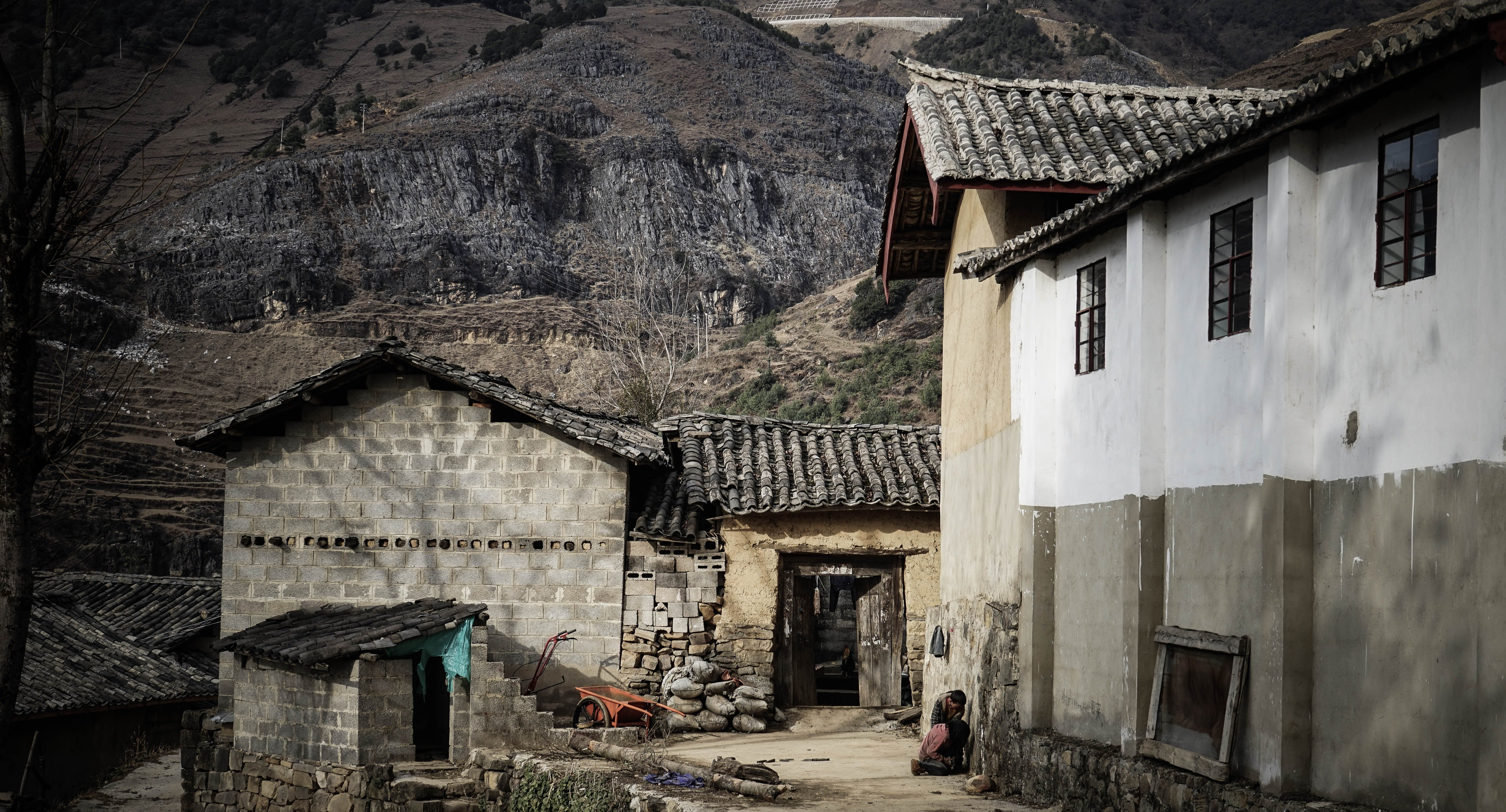 Pictured - A village near a mountain cliff   Source: Pexels