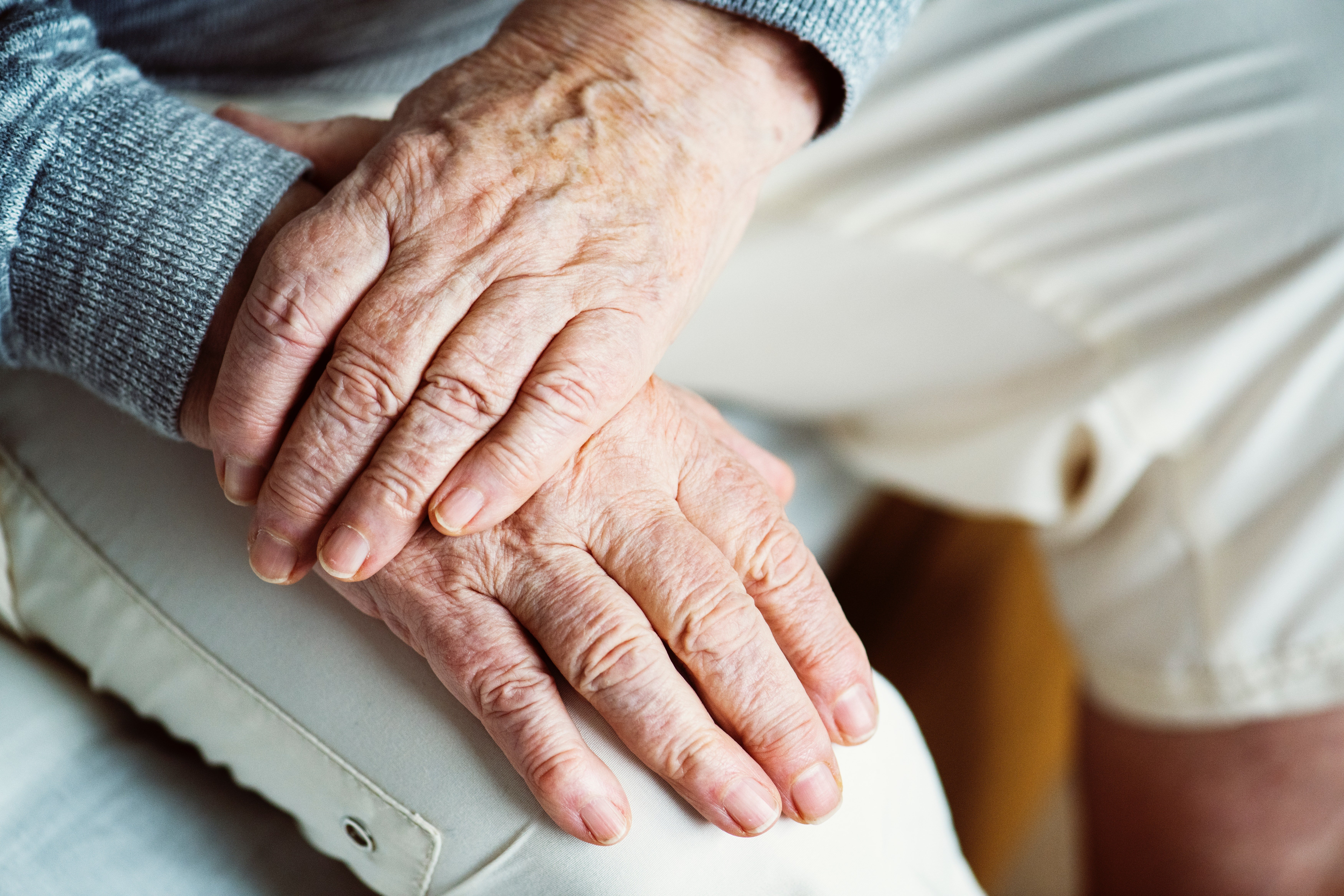 An old man places his one hand over the other. | Source: Pexels