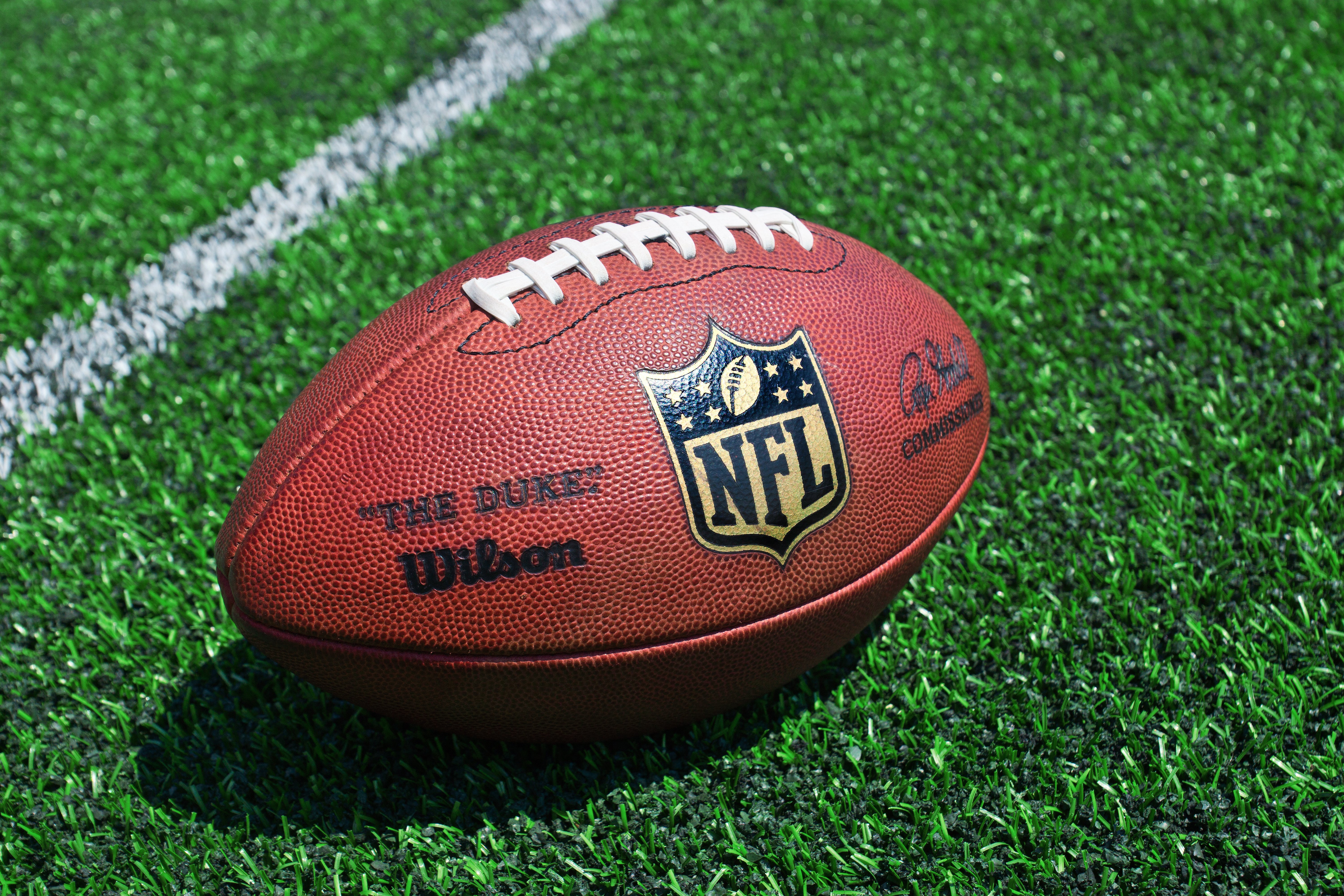 Photo of official NFL football on field. Source: Shutterstock
