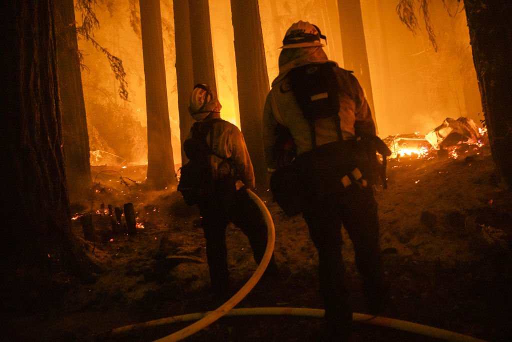 Firefighters with the Jamison Creek CDF station protect a home on Acorn Drive as flames approach during the CZU Lightning Complex fire | Photo: Getty Images