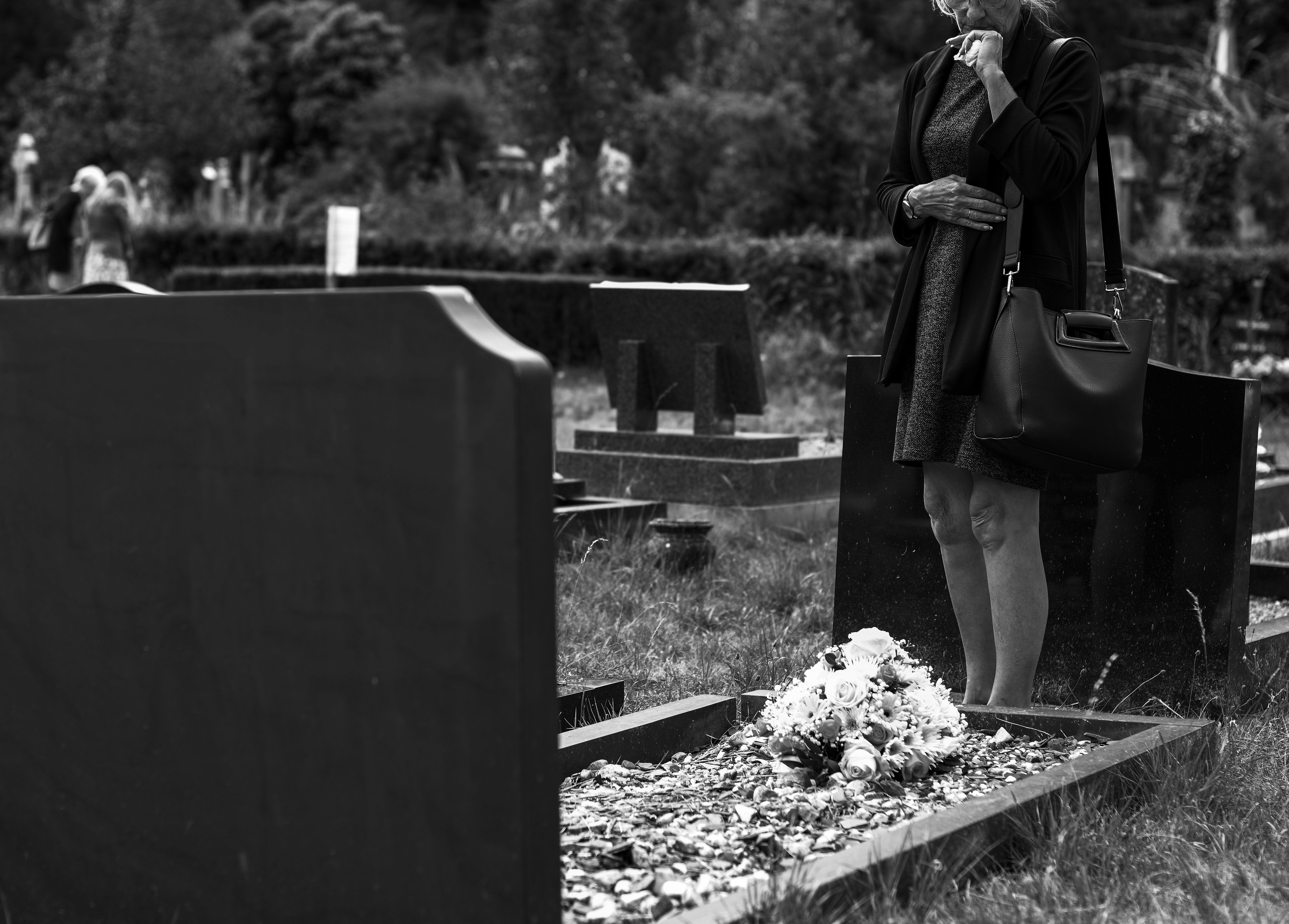 Woman grieving in front of a tombstone | Photo: Pexels