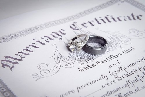A close up of a marriage certificate and wedding bands. | Source: Shutterstock.