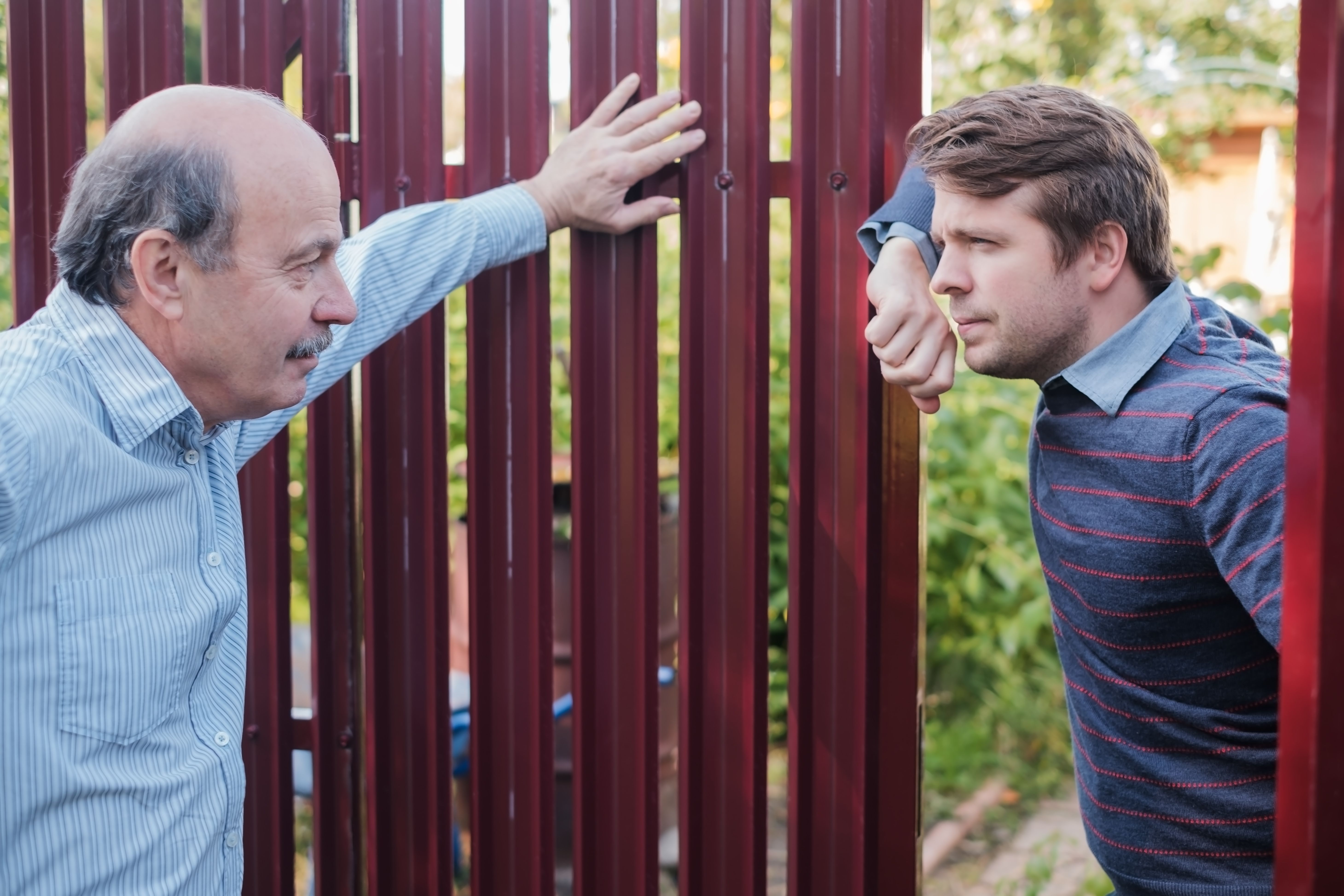 A father and son looking at each other in the yard.   Source: Shutterstock