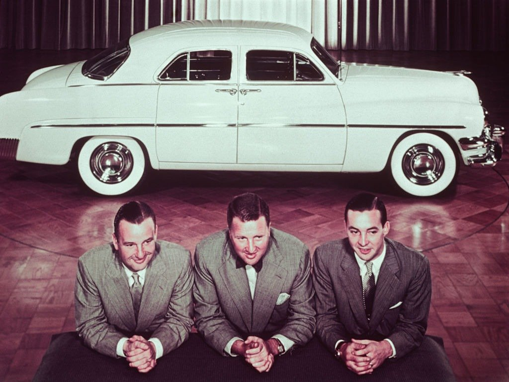 Henry Ford II, with brothers, Benson, and William Clay posed in front of 1950 automobile, circa 1950 | Photo: Getty Images