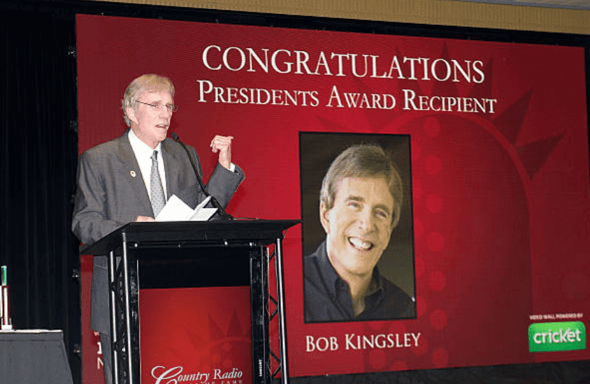 Bob Kingsley reads a speech as he receives the Presidents Award at the Country Radio Hall of Fame Dinner & Ceremony, on February 21, 2012 in Nashville, Tennessee | Source: Getty Images (Photo by Beth Gwinn/FilmMagic)