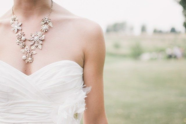 A woman in a wedding dress and necklace.   Source: Pexels