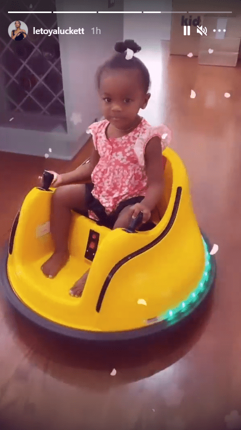 LeToya Luckett's daughter, Gianna, dressed in a cute pink dress while riding a yellow bumper car | Photo: Instagram/letoyaluckett