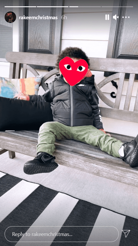 A picture of Jasmine Jordan's son, Rakeem, seated on a bench with his face covered with a red heart emoji  | Photo: Instagram/rakeemchristmas
