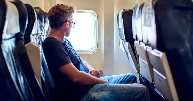 Daily Joke: Agent, Black Labrador Retriever, and a Man Settle in Their Seats on a Plane