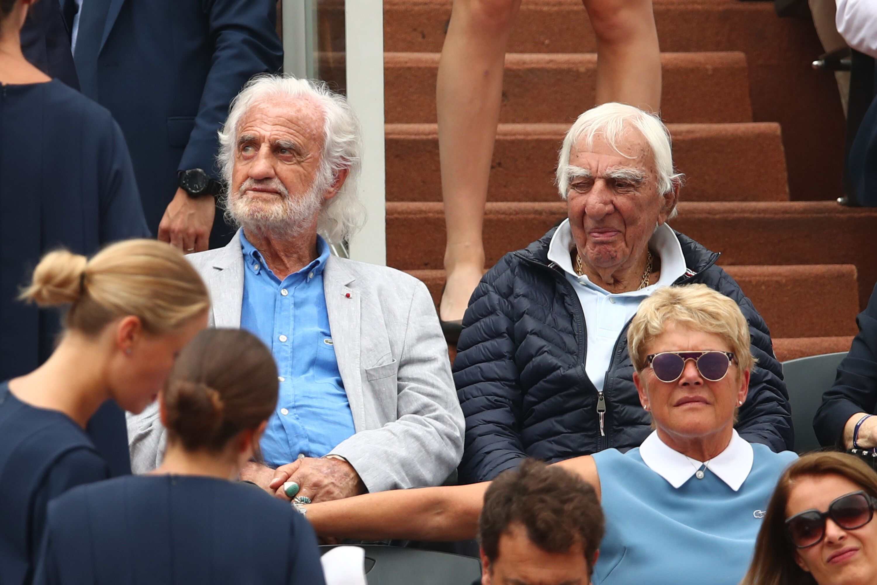 Les acteurs français Jean-Paul Belmondo et Charles Gerard regardent la finale du simple masculin. | Photo : GettyImage