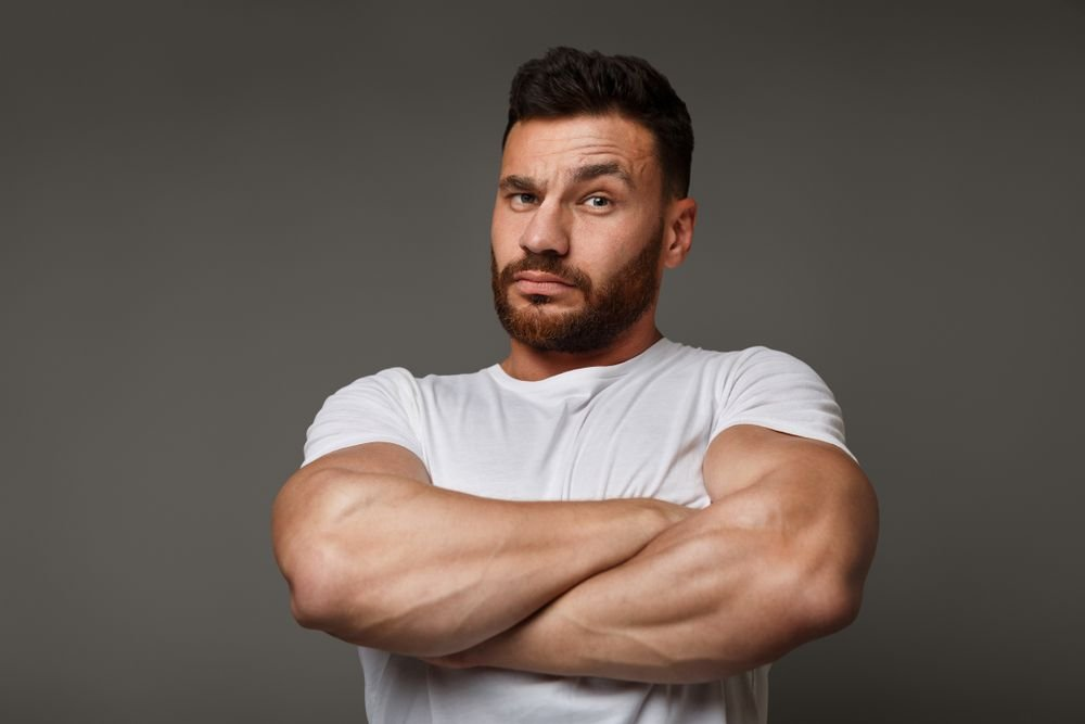 A man looks angry with his arms crossed. | Source: Shutterstock