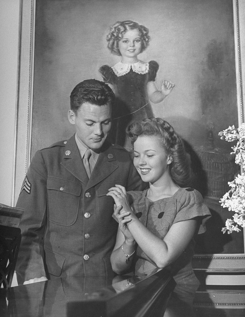 Shirley Temple and Sgt. John Agar, looking at the ring on her finger. | Source: Getty Images
