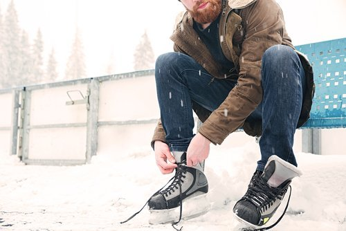A man tying the laces on his skates. | Source: Shutterstock.