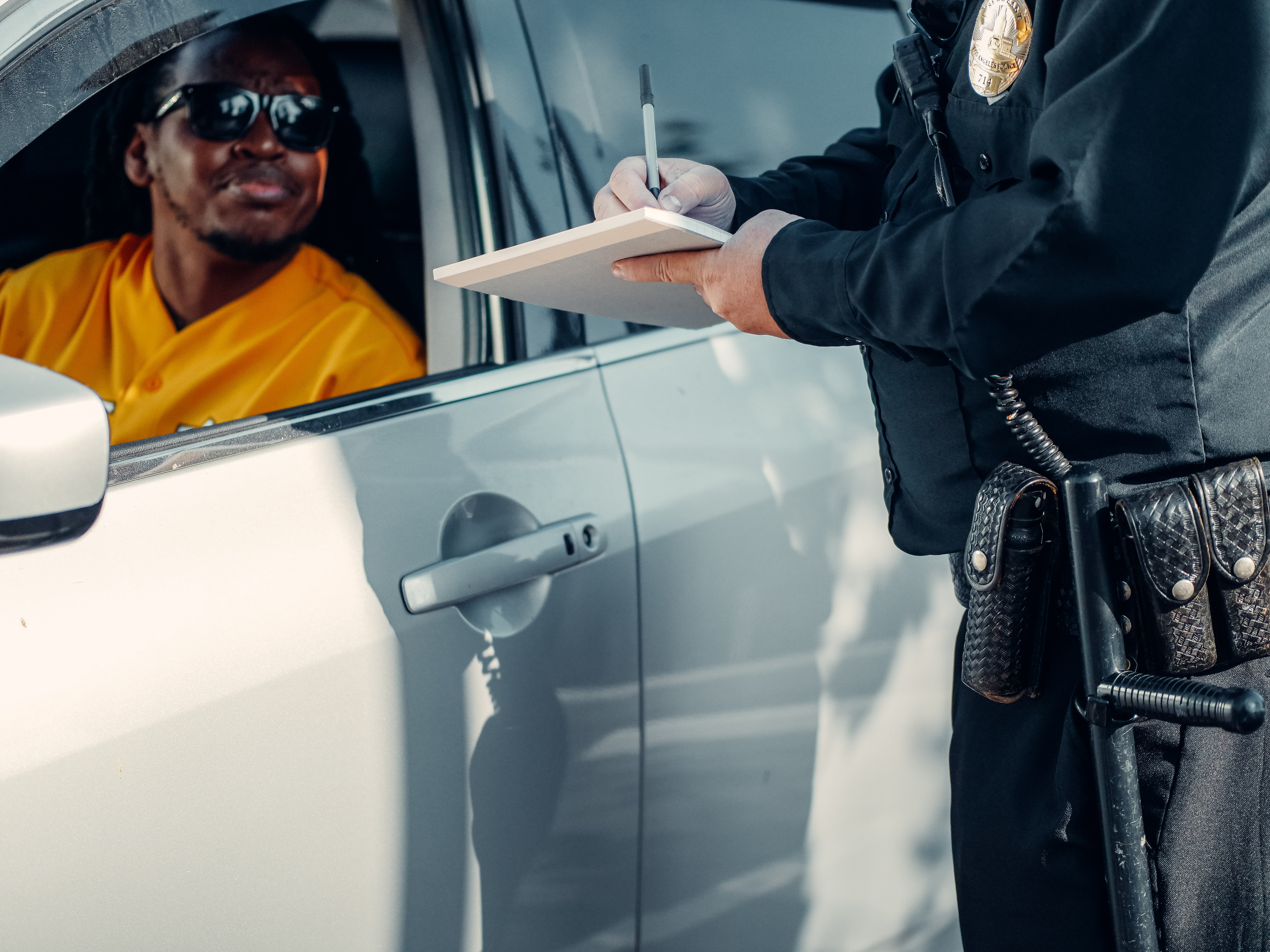 A police offficer writing out a ticket for a man in a car.   Pexels/ Kindel Media