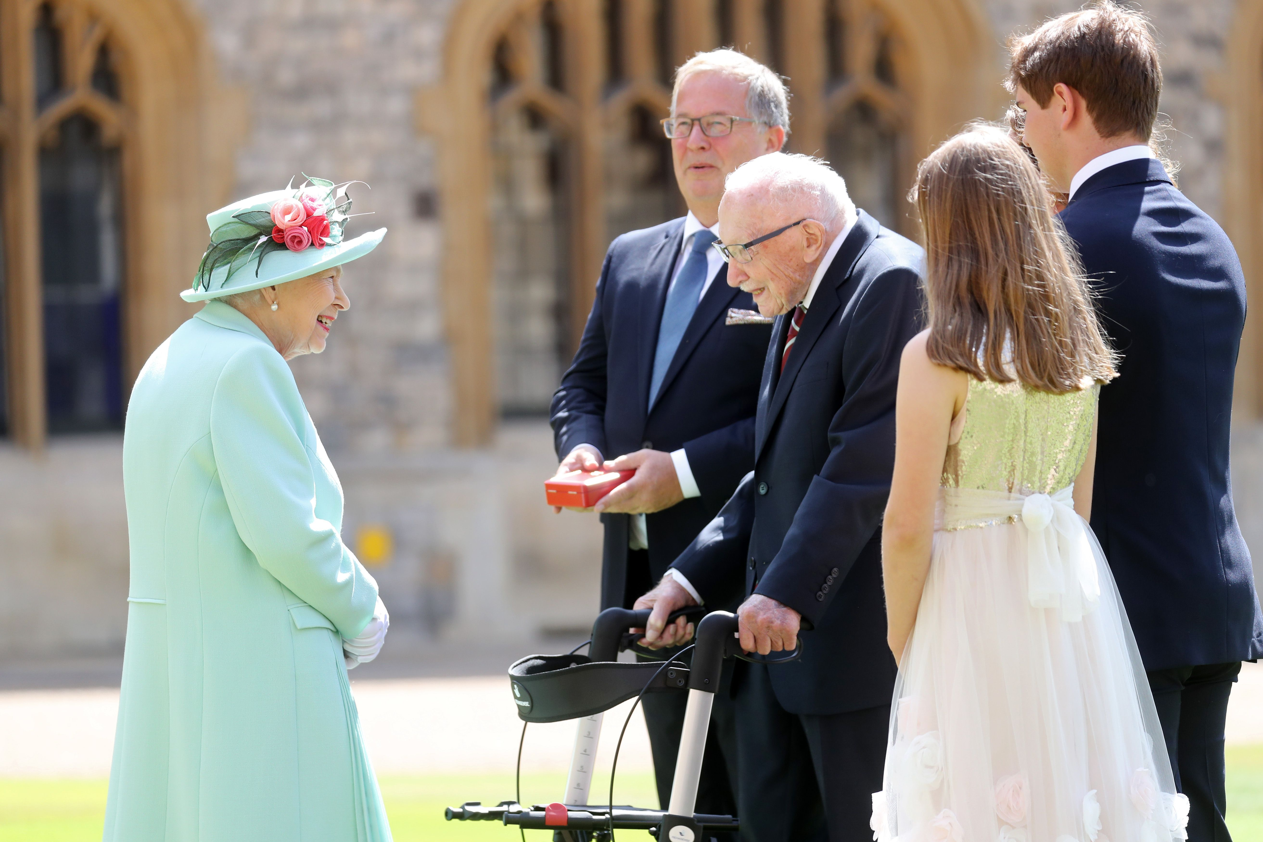 Queen Elizabeth II talks Captain Sir Thomas Moore and his family after awarding him with the insignia of Knight Bachelor at Windsor Castle on July 17, 2020 in Windsor, England.   Photo: Getty Images