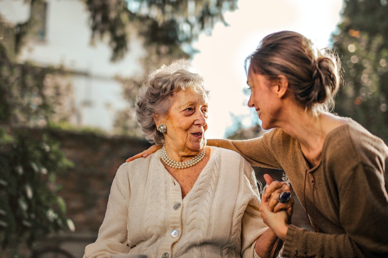 Woman sitting with elderly mother   Source: Pexels