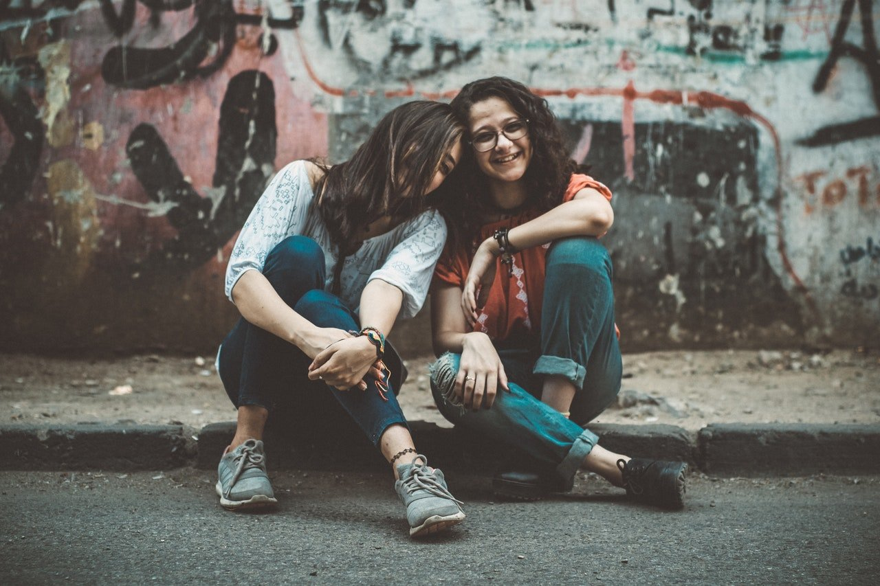 Photo of two ladies sitting by the road | Photo: Pexels
