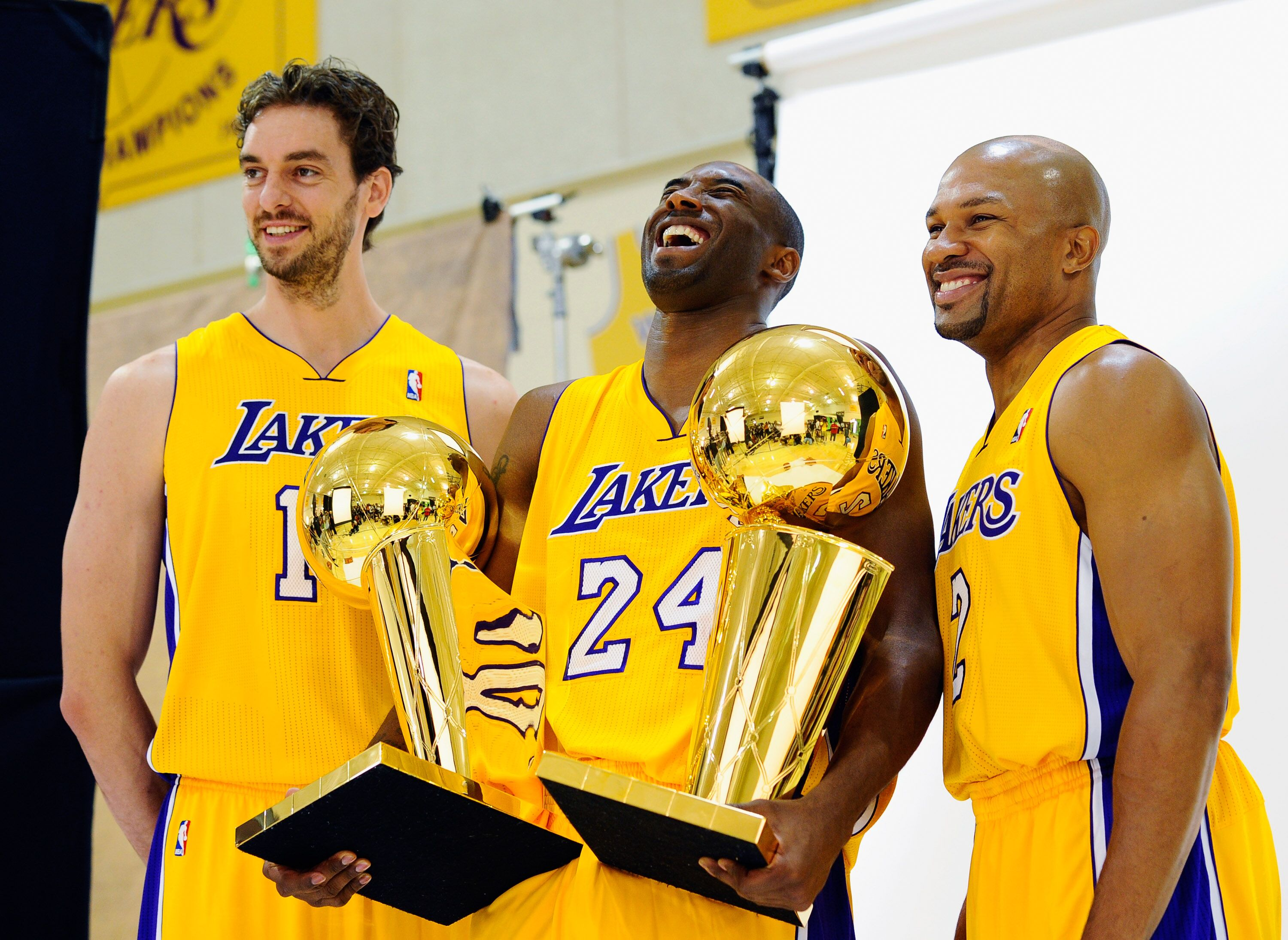 Kobe Bryant #24 of the Los Angeles Lakers laughs as he holds two NBA Finals Larry O'Brien Championship Trophy's as he poses for a photograph. | Source: Getty Images