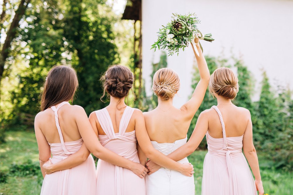 A bride standing with her back and raising her hand with three bridesmaids. | Photo: Shutterstock.