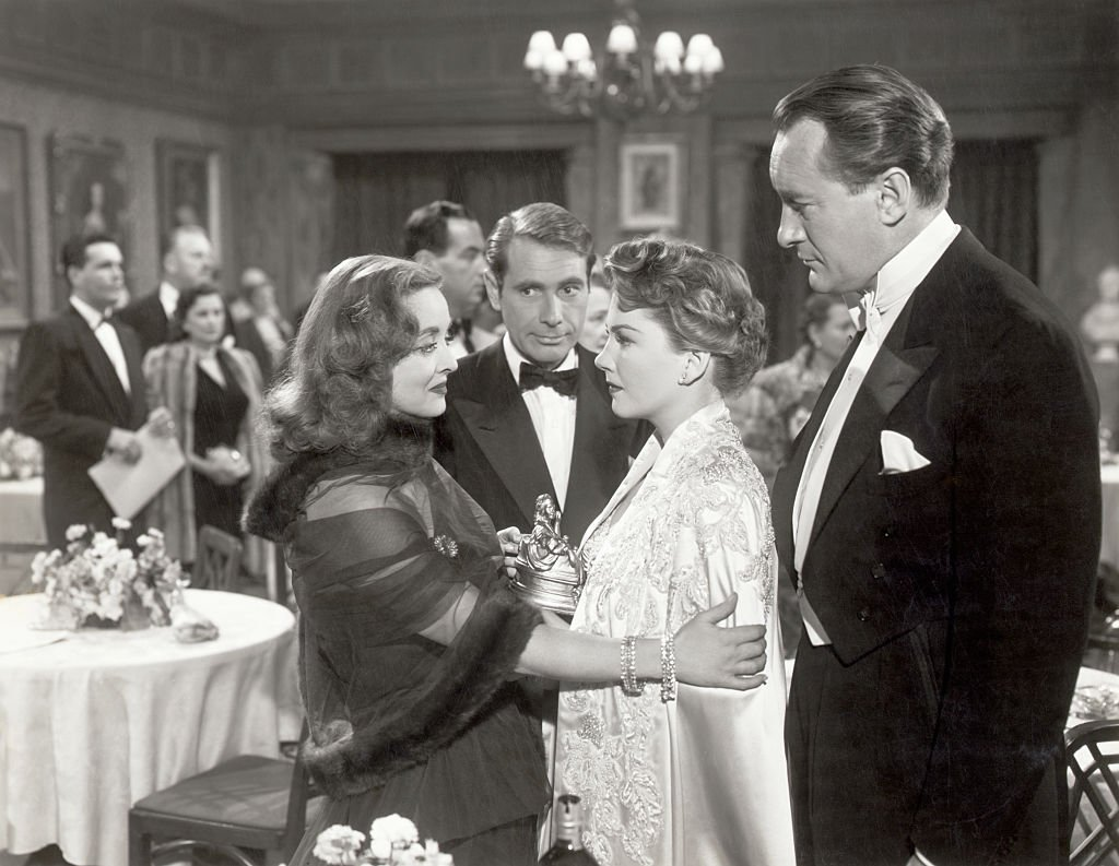 """Bette Davis, Gary Merrill, Anne Baxter and George Sanders during a scene from Darryl F. Zanuck's Production """"All About Eve"""", a 20th Century Fox picture. Undated movie still.   Photo : Getty Images"""