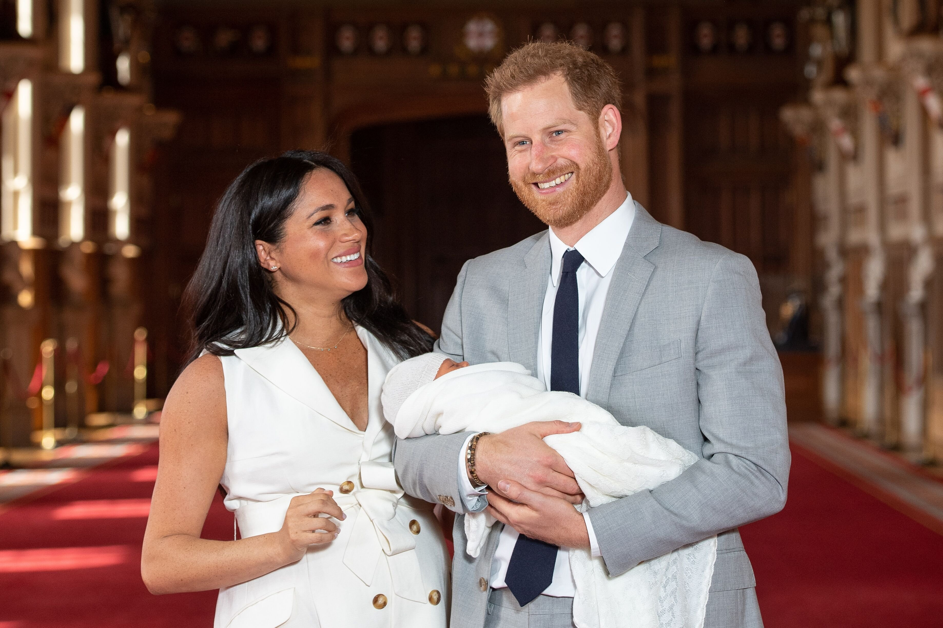 Prince Harry and Duchess Meghan pose with their newborn son Archie Harrison Mountbatten-Windsor during a photocall in St George's Hall at Windsor Castle on May 8, 2019 in Windsor, England. | Source: Getty Images
