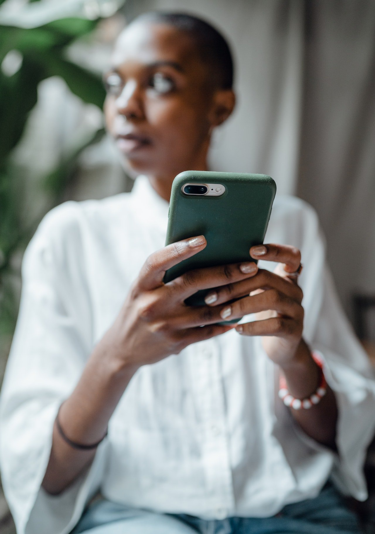 Woman using her phone and looking away   Source: Pexels
