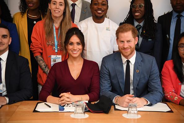 Meghan Markle en jupe rouge en cuir et le prince Harry la conduit au château de Windsor