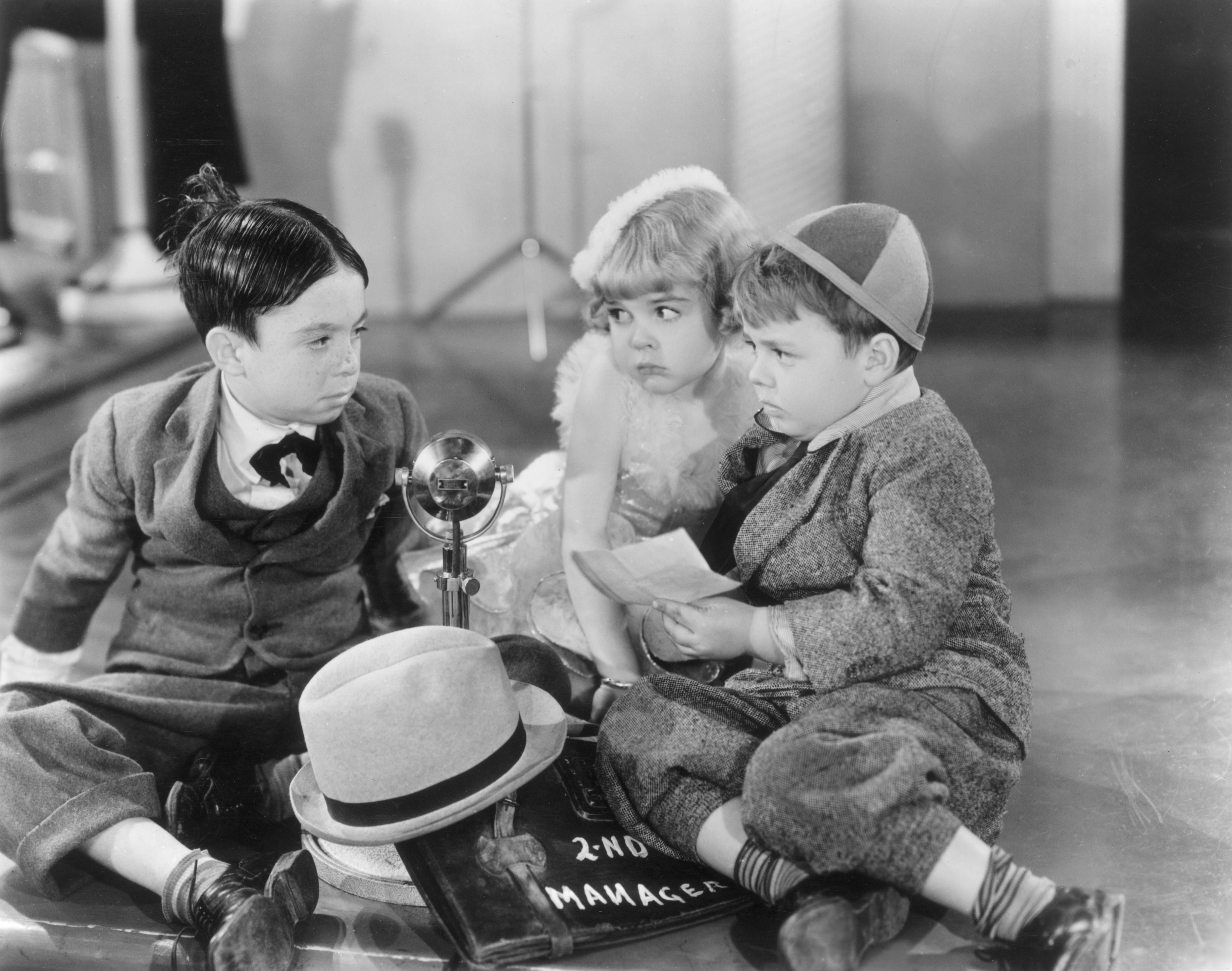 American child actors Carl Switzer (as Alfalfa), Darla Hood and George McFarland (as Spanky) sit on the floor around a microphone in a still from director Fred C. Newmeyer's 'The Pinch Singer,' one of the Our Gang film series | Source: Getty Images