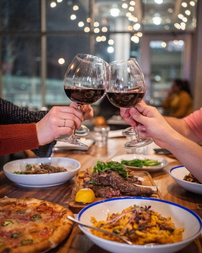 Four hands holding glasses of wine and food on the table | Source: Unsplash