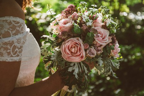 Bride holding her boho wedding flower bouquet. | Photo: Shutterstock