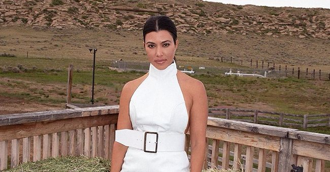 Kourtney Kardashian Poses in a White Dress & Shows off Her Fit Figure with a Massive Waist Belt
