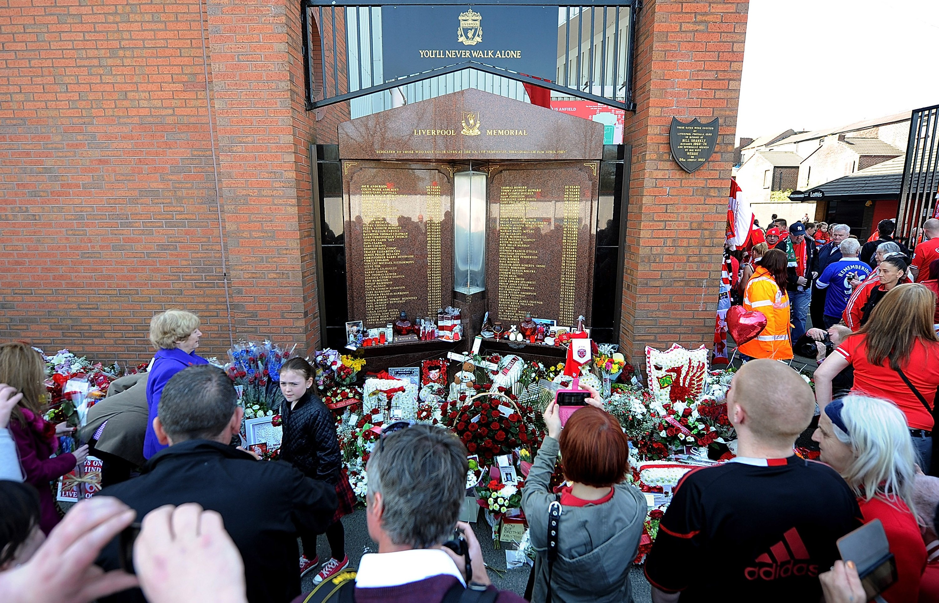 Fans gather at the Hillsborough memorial during the memorial service marking the 25th anniversary of the Hillsborough Disaster, at Anfield Stadium on April 15, 2014 in Liverpool, England. | Source: Getty Images