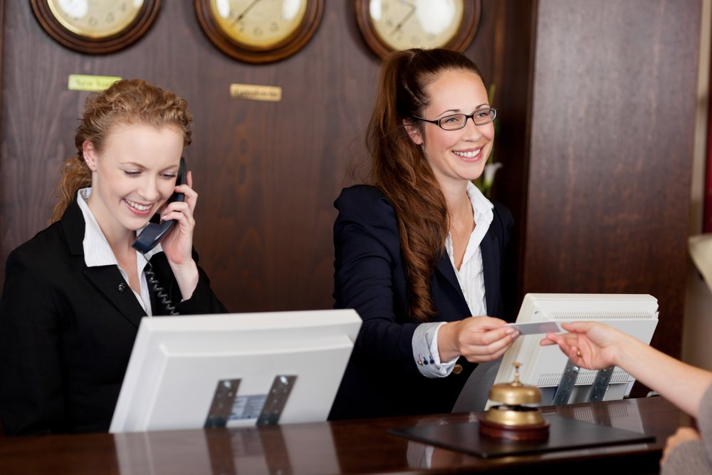 A photo of two receptionists at a reception desk   Photo: Shutterstock