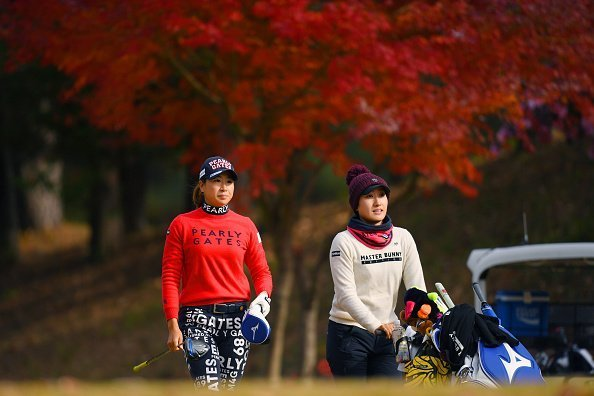 A golfer and her caddie pictured having a walk during the final round of the Japanese LPGA Final Qualifying Tournament | Photo: Getty Images