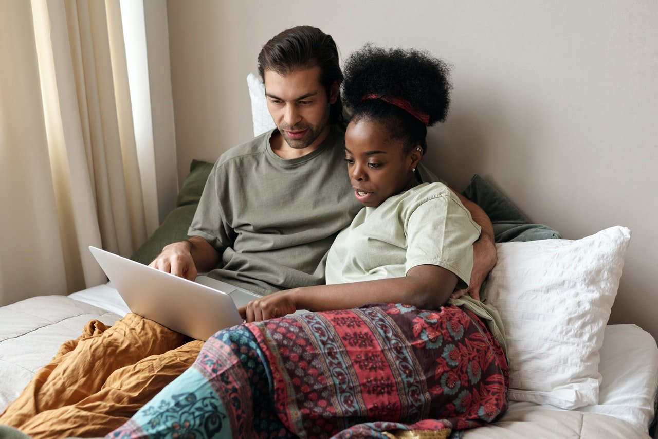 Photo of couple with a laptop in bed | Photo: Pexels