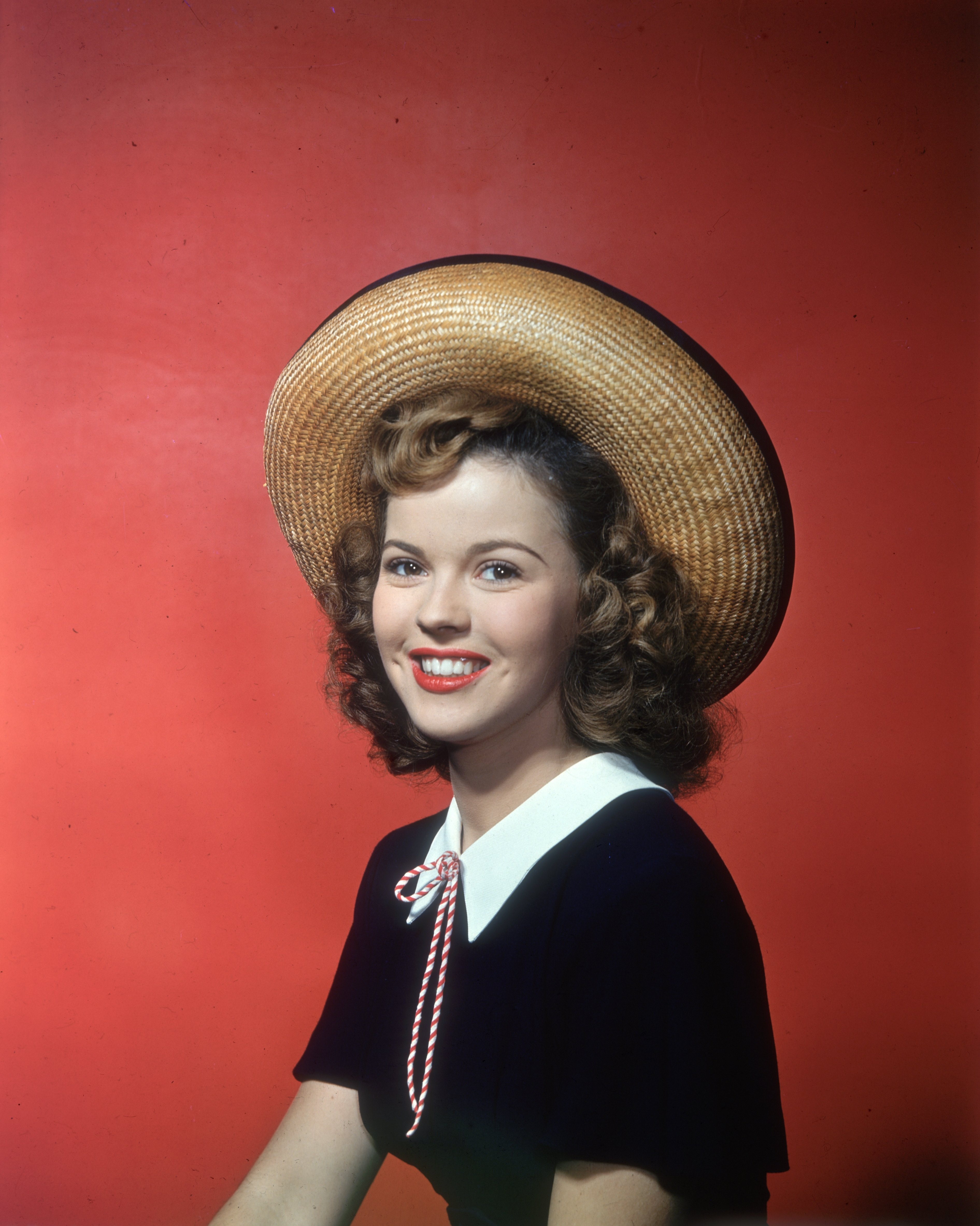 Smiling studio portrait of American actor Shirley Temple, sitting in front of a red backdrop, wearing a straw hat and black top with white collar. circa 1945 |Source: Getty Images